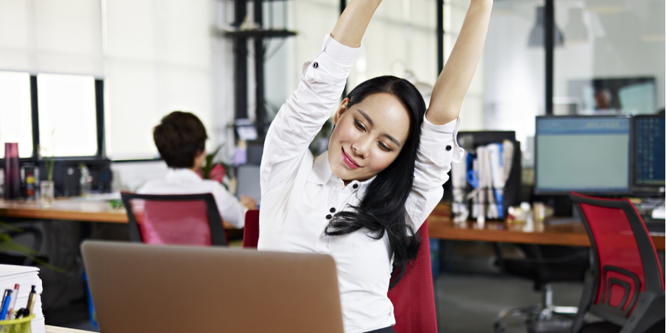looking at work on laptop computer with satisfaction and stretching arms in the air.